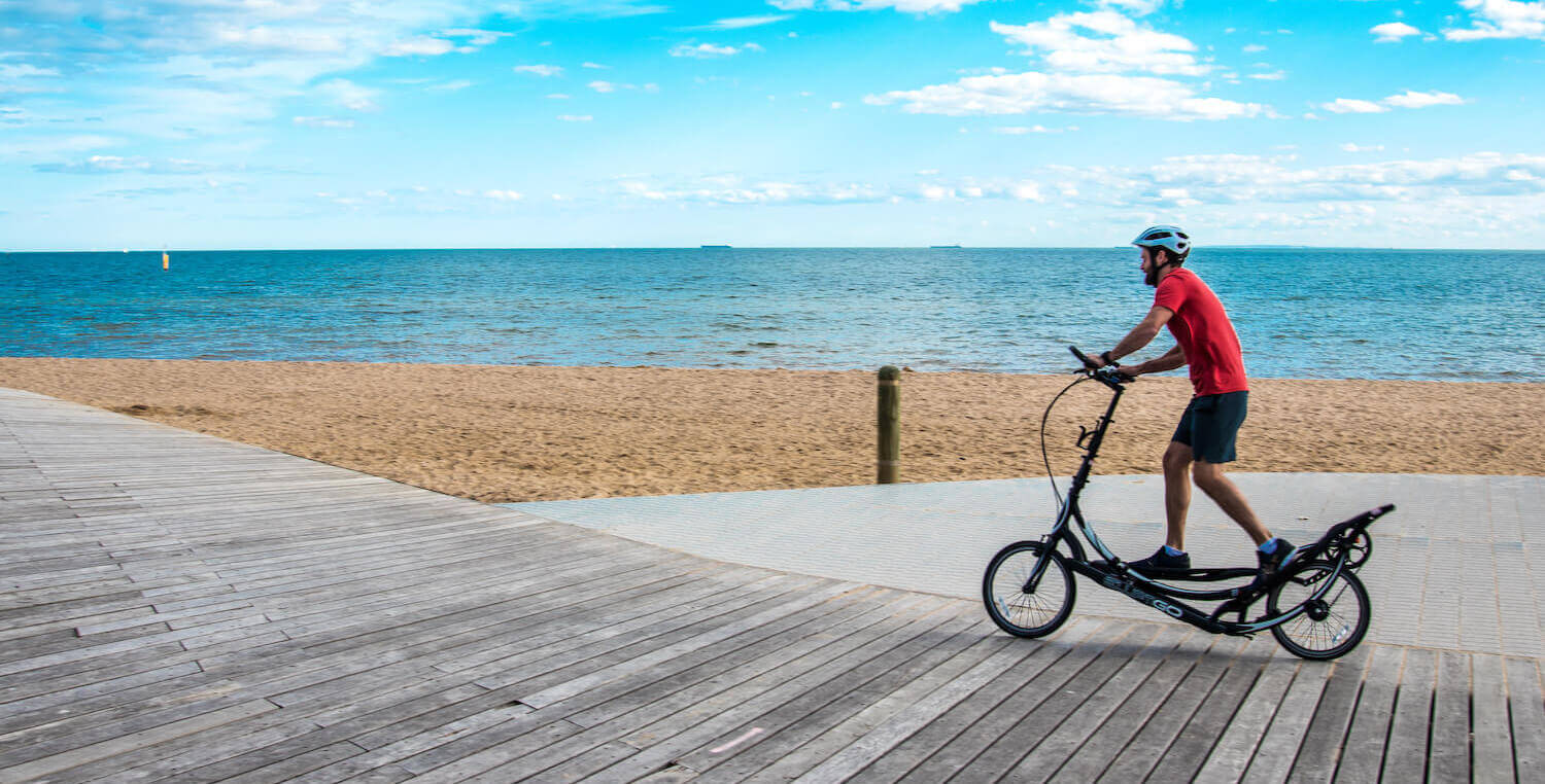 Man riding elliptigo along the foreshore